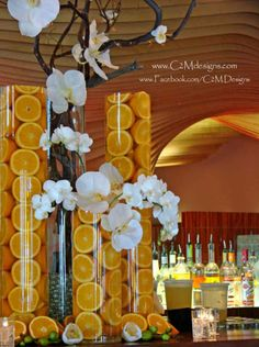 Manzanita in cylinder vases with phalenopsis orchids and fresh oranges.  Designed by: Christine McCaffery. www.c2mdesigns.com