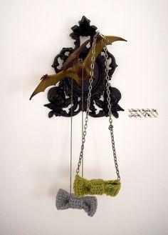 petit cadre de plastique doré avec image religieuse, bombé en noir mat et dinosaure collé au pistolet pour accueillir les colliers d'Adèle Blanc-Sec…  (via le petit Yaka moderne: expo déco, deuxième épisode: cadres)