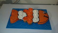 Easy Nemo cake. 12 cupcakes in the middle. 1 round cake, halved, for the head and tail (tail portion shaped).