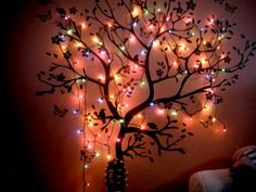 Another grand idea for home mood lighting: branchy tree full of butterflies & flower blossoms, painted simply on a bedroom wall, this time with rainbow Christmas lights all strung up. Super cute for both kids AND adults young at heart.