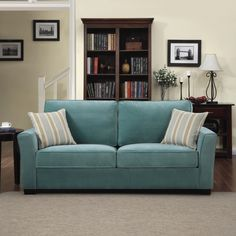 The Portfolio Home Furnishings Tara sofa features flared arms in a turquoise blue velvet fabric. The Portfolio Tara sofa includes two decorative stripe pillows in shades of aqua, taupe and cream.