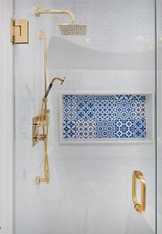 Wonderfully designed seamless glass shower boasts a brass door handle complementing a brass shower kit fitted with a square rain shower head fixed to white grid wall tiles.