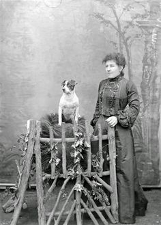 History in Photos: Adam MacLay. Outdoors portrait in front of false backdrop, unidentified woman with high neck collar dark embroidered blouse, standing with old Jack Russell Terrier dog, 1905-26