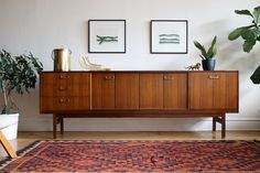 Mid-century modern teakwood credenza made by G-Plan in the U.K. Features accordion doors in the center with shelving.