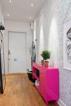różowa komoda nowoczesna,tapeta w czarno-białe drobne wzorki,lusro podłogowe w czarnych ramach,nowoczesne grafiki na ścianie