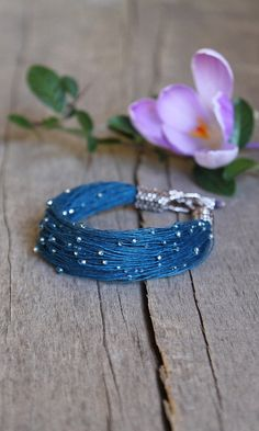 This delicate bracelet for women is a really eyecatching accesory. It features over 100 thin linen threads with tiniest seed beads in lovely silver color. Very feminine piece of summer jewelry. Be not only fashionable but also unique with Naryajewelry handmade bracelets!