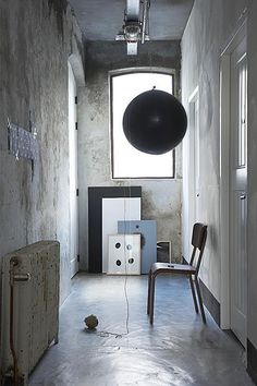 A big black balloon in an industrial concrete hallway (source: vtwonen mrt2012  Styling: Esther Jostmeijer  Fotografie: Dennis Brandsma)