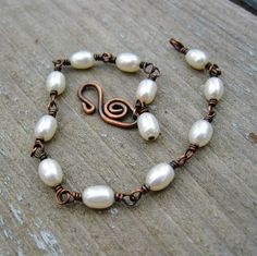 This bracelet is a simple classic design, with creamy white freshwater pearls. Each pearl is wire wrapped with antiqued copper to form each link, and an extra pearl dangle is added at the end. Very light in weight and comfortable to wear.    Handcrafted clasp has been shaped, tumbled to strengthen, antiqued, and polished.    Total length is approx 7 3/4 inches.      B12304