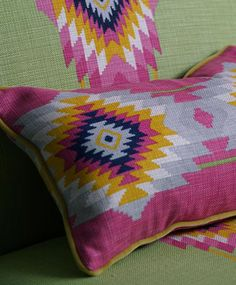 With definite funk, Cruz from Andrew Martin, pink and green Aztec style fabrics perfect for a contemporary teenage bedroom.