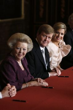 Prince Willem-Alexander of the Netherlands sits alongside his wife Princess Maxima (R) during the abdication ceremony of his mother Queen Beatrix of the Netherlands (L) in the Moseszaal at the Royal Palace on 30 April 2013