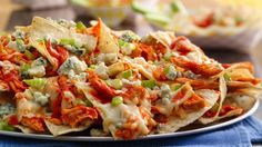 A mountain of nachos made with everyone's favorite spicy Buffalo wing sauce and blue cheese!