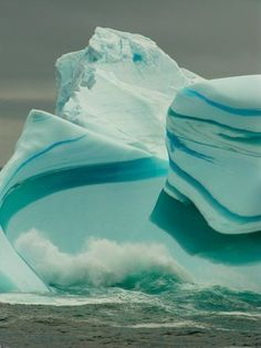 Icebergs sometimes have stripes, formed by layers of ice deposited on different conditions. Blue stripes are created when a crevice in the ice sheet fills up with melted water and freezes so quickly that no bubbles form. Green stripes form when an iceberg falls into the sea and a layer of water rich in algae freezes onto the bottom.  Brown, black and yellow lines are caused by sediment, picked up when the ice sheet grinds downhill towards the sea.     (Photos: Antarctica Series by Steve…