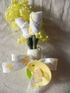 This is a gorgeous gift to give to a mommy-to-be, daddy-to-be, or grandparents-to-be. It is a baby shower corsage made to look like roses that is wrapped and tied off with a beautiful ribbon.    This elegant gift is created with a pair of baby socks that are made to look like roses, accented with some silk flowers. The pair of roses is then wrapped with one washcloth, one 0-3mo pacifier, and tied off with beautiful ribbon.