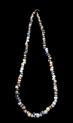 A large Eastern Mediterranean glass eye bead necklace  Circa 6th-2nd Century B.C. Composed of one hundred and four largely Phoenician globular beads, in various shapes, sizes and colours, including dark and light blue, yellow, turquoise, red, white and green, with blue 'eyes', strung on wire