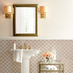 Vintage Glam Bathroom —Adding glamorous gold touches to your bathroom takes it from classic to class act. Antique sconces, a hammered mirror and brass hardware work together to give off a warm gold glow. A statement-making metal table styled with faux florals, towels and bath essentials fills the space with character.
