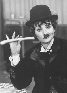 Comedienne/actress Lucille Ball holding a breadstick like a cigar doing an imitation of Charlie Chaplin on her New Year's TV show