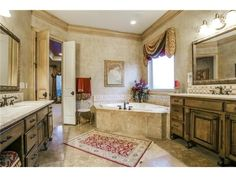 Master bathroom // Dual vanities with granite countertops, jetted tub under a large window