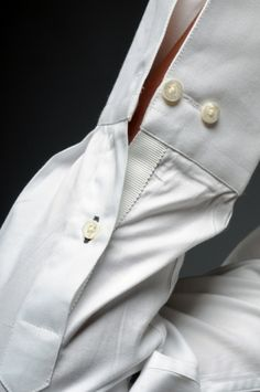 A close up of the white grosgrain adorning the cuff sleeve's placket.