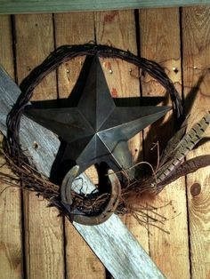 Barbed wire with tin star, love it! Could probably use dried blue bonnets or wheat in place of the feathers even..