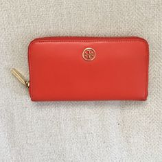Gorgeous orange Tory Burch Wallet!! Tan inside Gorgeous orange Tory Burch Wallet!! Tan inside, gold emblem and zipper. Great condition, little marks noticeable on bottom side. No trades. Thanks!! Tory Burch Bags Wallets