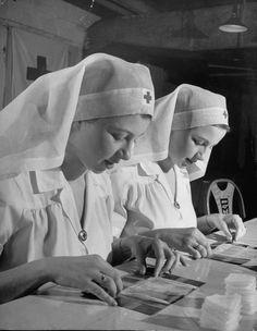 Twin teenage girls working as Red Cross volunteers, rolling bandages, 1940's Life Magazine ~