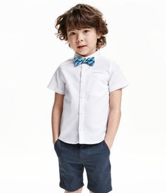 Short-sleeved shirt in woven cotton fabric with a turn-down collar and welt chest pocket. Matching tie/bow tie with adjustable elastic strap.