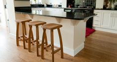 Oak bar stools with bent legs and sculpted seats.