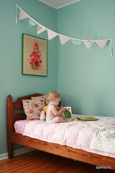 Un somptueux vert pâle aux murs de la chambre de Bébé est adouci par des touches de rose, pour une ambiance romantique et champêtre à souhait.