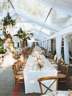 drapé plafond couleur blanc, table rectangulaire en bois, nappe de table blanche avec des lustres baroque en fleurs