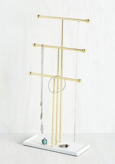This triple-tiered jewelry stand is at your service! Hang your accessories over the gold bars of this metal tree, or let your precious pieces rest atop its glossy white base. Any way you display your adornments, this organizer delivers form and function like no other!
