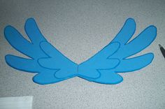 Good picture of some home made wings for Liv's Rainbow Dash costume.  Maybe I could make them out of blue poster board or some blue felt glued to poster board???  Then attach with elastic? Hmmmm