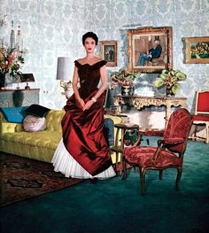 Babe Paley photographed at home wearing Charles James' red silk evening gown, 1946.