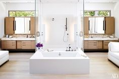 In the master bath, Caesarstone-top vanities flank the shower; the sinks and the tub by MTI Baths have Graff fittings.