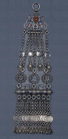 Dagestan | Women's pendant in niello (a metal alloy that contains sulfur, copper, silver and often lead) and other materials | In Private Collection.  Image © De Agostini / A. Dagli Orti