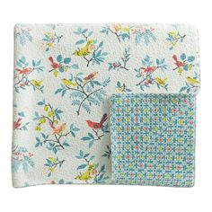 Tilly quilted throw with an all over bird design with jigsaw quilting pattern with reverse and bound edge showing floral leaf design. Throw is made with 52% of polyester and 48% of cotton.