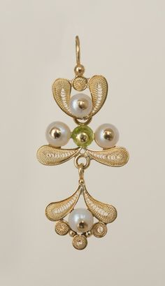 The 18kt filigree pendant, with its lustrous pearl and 18kt gold filigree petals, may be detached. The repoussé flower top with a white pearl center may be worn alone