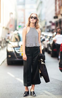 A gingham halter top with a peplum is worn with cuffed black pants, mules, and tortoiseshell sunglasses