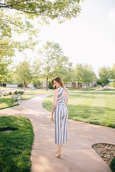 Blue and white striped jumpsuit styled for Spring with a straw clutch and red lipstick by Lauren Cermak of Going For Grace. Timeless Fashion, Fashion Beauty, What To Wear To A Wedding, Spring Summer Fashion, Spring Style, Meghan Markle Style, Gingham Fabric, Kate Middleton Style, Striped Jumpsuit