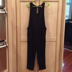 Black jumper Black sexy jumper. NWOT never worn. Sides are open and the back is a cutout with a tie at the top. I took pictures the best I could I what it looks like. It's super cute on. Size XS. Pants Jumpsuits & Rompers
