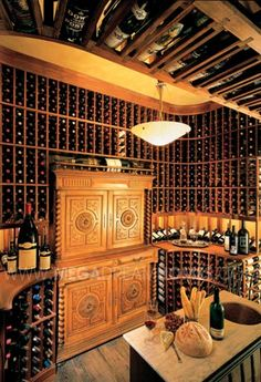 Two story wine cellar with overhead storage and an antique, hand-carved armoire serving as the focal point of the room. Brings a whole new meaning to being a collector! #wine room #antique #winery