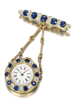 SAPPHIRE AND DIAMOND WATCH, CIRCA 1900  Round watch dial with Roman numerals, bezel adorned alternating round diamonds and sapphires, suspended by chains in an ornate gold bar oval sapphires and diamonds.