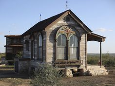 This shabby chic cottage was made from 95% of salvaged materials from 25 other houses, with some of them being as old as 200 years (yet still in fantastic condition). Created by Texas Tiny Houses, this 12 by 18 foot house features insanely gorgeous arched stained windows, a ladder leading to the upper round sleeping area, a rustic style kitchen and a spacious living / dining area.