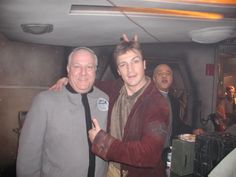 On the set of Firefly. Ron Glass is giving Nathan Fillion rabbit ear. That is all.