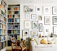 Eclectic living room with color coordinated built in bookcases, gallery wall, and beadboard ceiling.