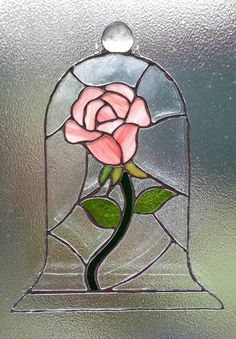 This stained glass rose in a bell jar is made using the Tiffany copper foil method by me in my small studio. Each piece is individually cut then ground to ensure a perfect fit and then foiled and soldered into place. The glass on the rose has been cut in such a way as to use the patterning in the glass to give more dimension and depth to it. The top is adorned with a large glass pebble and it has almost invisible strong fishing wire to hang it in your desired location. This piece is quite…
