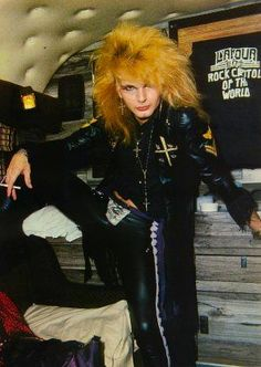 Rikki Rockett (Poison, drums), glammed up with 1980s pink hair, smoking a cigarette, but staring you down with a 1970s-style attitude.