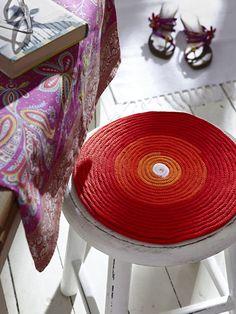 Originelle Idee für einen Hocker: Runde für Runde wächst aus einer Strickliesel das Material für eine Kissenauflage. Für diesen mehrfarbigen Strickschlauch wird Topflappengarn verwendet, wobei man nach Wunsch einfach die Farbe wechselt.