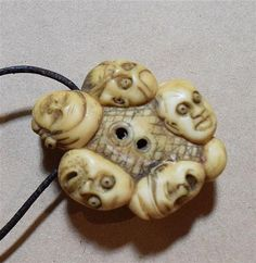 A carved ivory netsuke with twelve faces