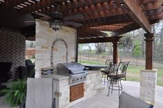 This outdoor kitchen has a focal wall separating it from the living area. Featuring a stone backsplash, BBQ, and bartop seating area. By Outdoor Signature in Argyle, TX