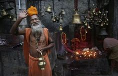 An Indian Sadhu, or Hindu holy man, waves to the camera at the Kamakhya temple in Gauhati, India, Saturday, June 21, 2014. The annual Ambubasi festival begins Sunday where hundreds of tantric Sadhus, holy men from an esoteric form of Hinduism, gather to perform rituals at the temple. (AP Photo/Anupam Nath)